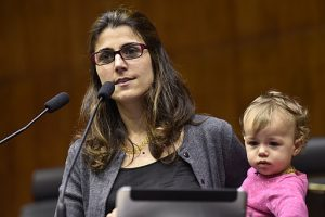 Woman with child speaking at public hearing